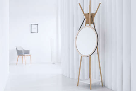 Mirror on wooden hanger against creative screen in white interior with grey chair