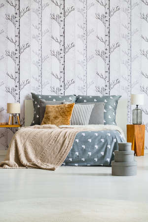 Grey Boxes Near King Size Bed With Brown Pillow Against Forest Wallpaper In  Bedroom With