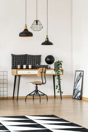 Three lampshades hanging above wooden desk with pillows, candles, potted plant, globe and typewriter