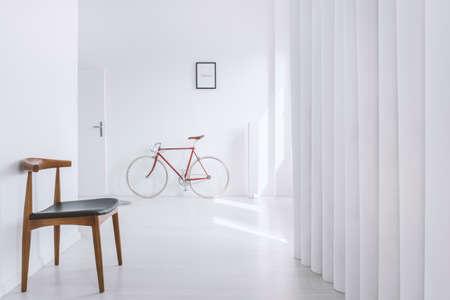 Classic wooden chair in empty antechamber with red bike next to door