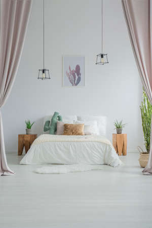 White stylish bedroom with pastel curtains, cacti, lamps and poster