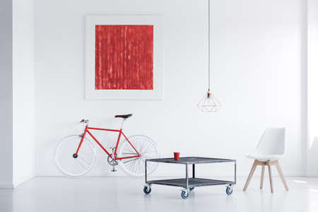 White chair at industrial table in white interior with red painting above bicycle