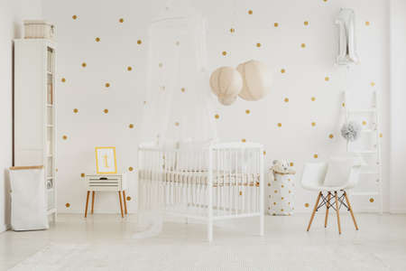 Two material baskets and small cupboard in bright baby room with white chair with pillow