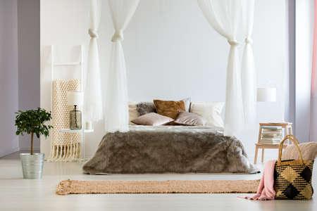 Lujoso interior de dormitorio contemporáneo con una manta de cama de piel extragrande y esponjosa, cortinas con dosel y almohadas decorativas Foto de archivo