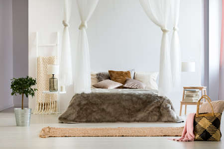 Luxurious interior of contemporary bedroom with fluffy oversized fur bed blanket, canopy drapes and decorative pillows