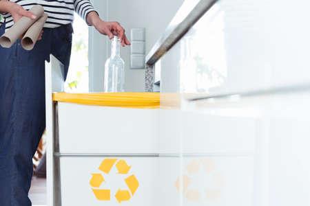Close-up van huisvrouw die afval in keuken scheiden door glazen fles in correcte container te werpen