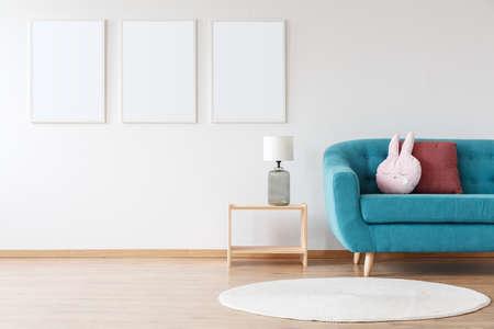 青いソファと白いカーペットが付いている子供の部屋の木製の腰掛けの白いポスターとランプのモックアップ