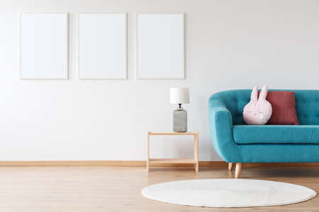 Mockup of white posters and lamp on wooden stool in child's room with blue sofa and white carpet Stock fotó