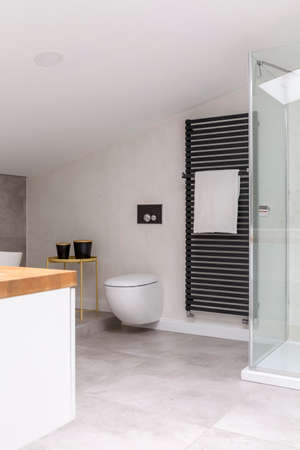 Simple elegant bathroom in the attic with toilet, washbasin cabinet and towel on black heater