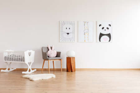 Drawings on white wall above grey chair with pillow and wooden stool in baby's room with white crib and rug Stok Fotoğraf - 97990224