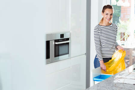 Smiling woman changing garbage bags in white kitchen with recycling bins