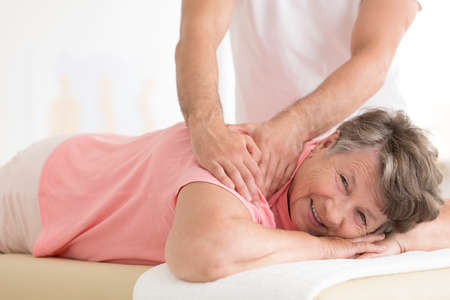 Elderly woman with pain lying on massage bed and masseur setting her shoulder