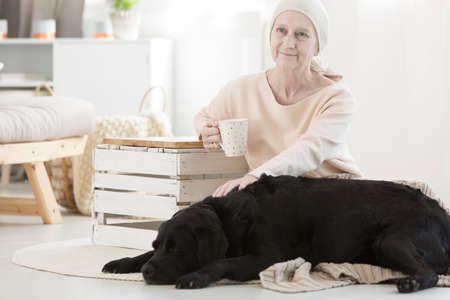 ペット療法の一部として彼女の犬友達を caressing 腫瘍高齢女性
