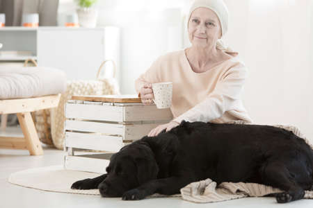 Elderly woman with tumor caressing her dog friend as a part of pet therapy