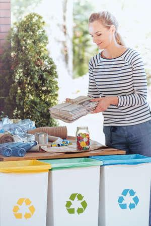 Mooie vrouw die zich naast recyclerende containers en sorterend afval op houten lijst bevindt