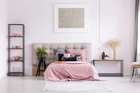 Pink quilt on bed with patterned pillows and copper lamp in stylish bedroom interior with metallic design Фото со стока
