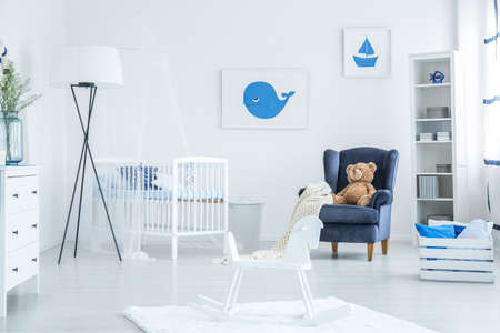 White rocking horse placed on the rug in simple baby room with dark armchair