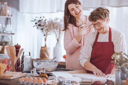 Kleindochter die van het koken met grootmoeder genieten terwijl status bij countertop met ingrediënten