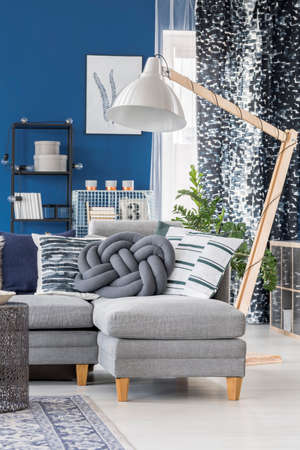 Blue apartment with big wooden lamp and decorative pillows on gray couch