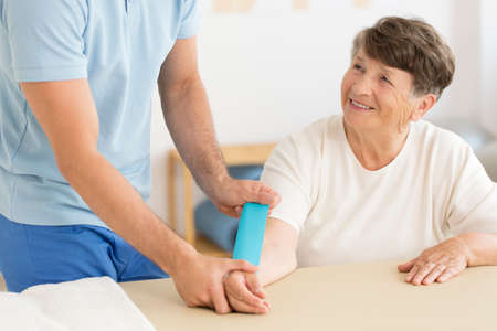 Smiling elderly woman sitting at desk and physiotherapist putting kinesiotape on her arm