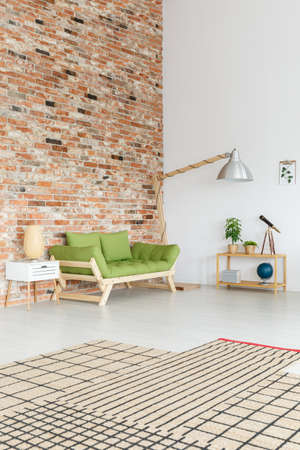 Handmade bamboo lamp shade on white cupboard in natural design studio interior with minimalist green sofa and plants Stock Photo