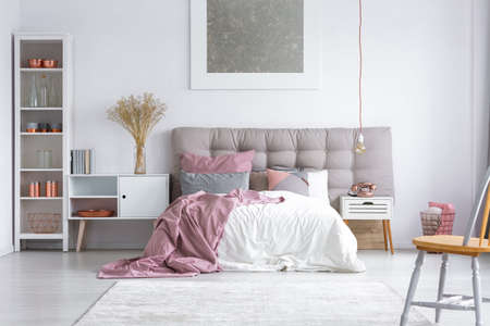 Spacious cozy master bedroom interior with copper decorations on the white rack, wooden chair and buttoned gray headboard