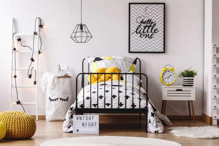 Orologio e pianta divertenti gialli sul comodino nella camera da letto del bambino bianco con il pouf giallo sul pavimento di legno Archivio Fotografico