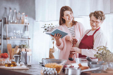 Grandmother and granddaughter have fun while cooking traditional food together  Stock Photo