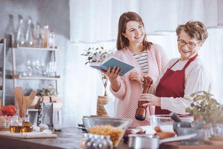 Grootmoeder en kleindochter hebben plezier tijdens het samen koken van traditionele gerechten