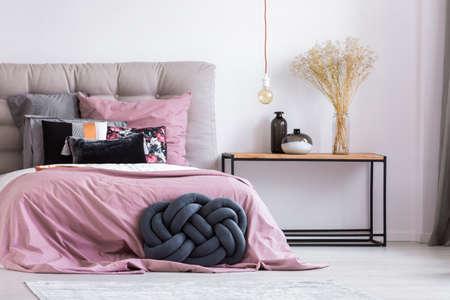 간단한 침실 장식으로 세련된 아파트에 핑크색 오버레이 침대 옆에 나무 머리맡 테이블과 파란색 수제 베개