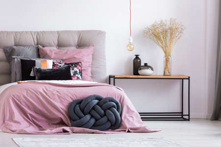 Wooden bedside table and blue handmade pillow next to bed with pink overlay in stylish apartment with simple bedroom decor Imagens - 90323771