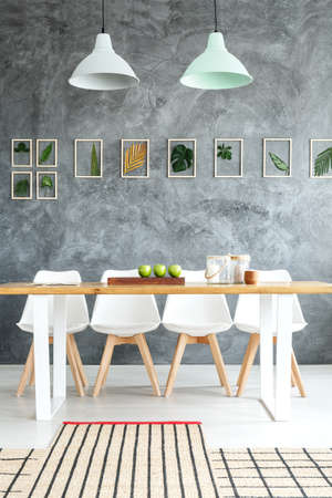 White designer chairs at wooden table in contemporary dining room with natural decorations and stylish asymmetric rug  Stock Photo