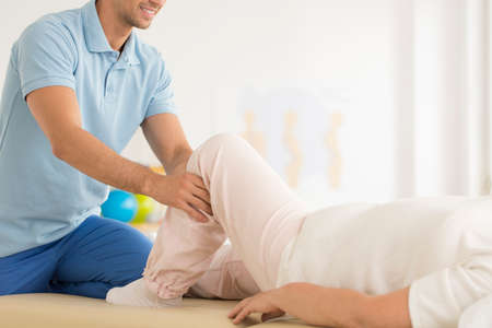 Physiotherapist helping in correct positioning of leg during meeting with patient Stock Photo