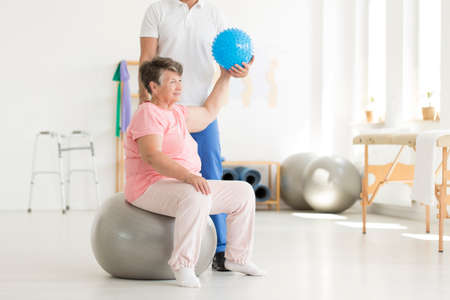 Happy senior woman sitting on grey ball and exercising in clinic using a blue ball