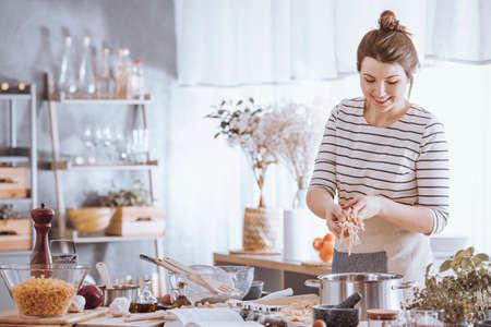 Glimlachende jonge vrouw die noedels toevoegen aan pot terwijl het koken in de keuken Stockfoto