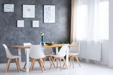 Bright dining room with wooden table and white chairs against concrete wall with paintings