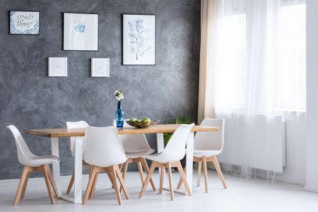 Lichte eetkamer met houten tafel en witte stoelen tegen betonnen muur met schilderijen