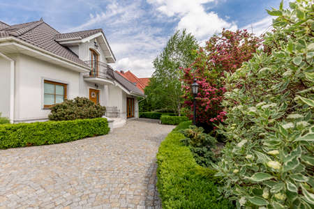 Driveway to a mansion with garden, trees and bushes on sunny day Stock Photo