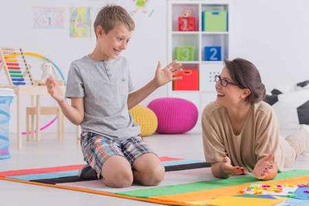 Female private tutor working with little boy teaching child to read using colorful letters Banque d'images - 97991239