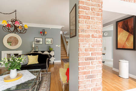 Flowers on glass table in spacious living room with brick support post and painting on the wall