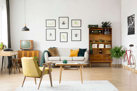Yellow chair at wooden table on white carpet in retro living room with television on cabinet next to sofa