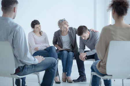 Psychotherapist supporting a man who lost his wife. Support group meeting for people in mourning Stock Photo