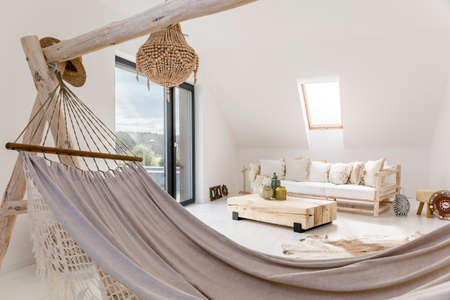 Grey handmade hammock standing in the white attic room with wooden sofa