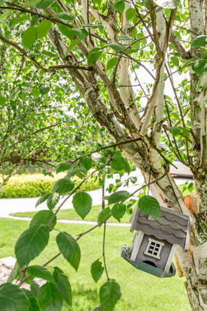 Small bird house suspended on a tree in the garden of a mansion
