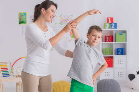 Child medical health concept, young boy stretching his body, exercising with professional female physiotherapist Stock Photo
