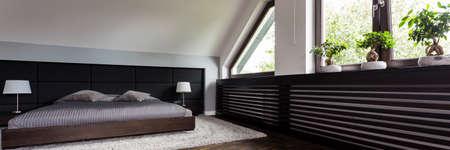 Scatto di una spaziosa camera da letto con un letto matrimoniale, progettato in colori scuri Archivio Fotografico - 90492227