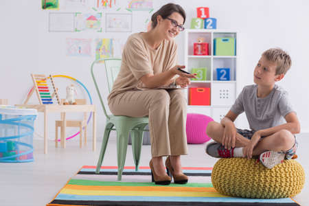 Professional child counselor during successful therapy session with little boy sitting on pouf in office room Stock Photo