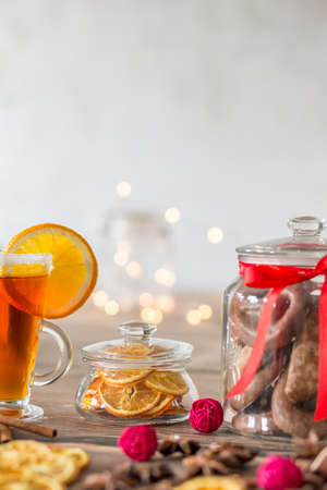 Slices of lemon in glass container on table with cup of tea during christmas time Stock Photo
