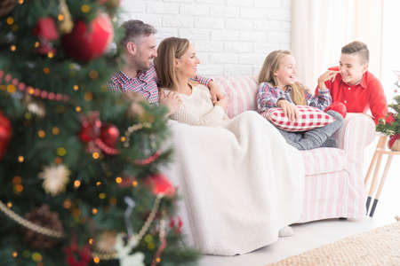 Young and happy family sitting on the couch during christmas Imagens