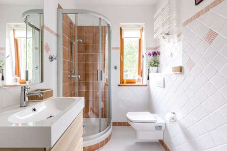 Glass shower in small white bathroom with sink, mirror and toilet